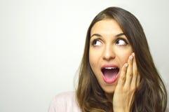 Удивленная молодая женщина смотря к стороне с открытым ртом с рукой на стороне на белой предпосылке Excited девушка смотря к s стоковые фотографии rf