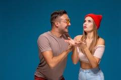 Удивленные пары в случайных одеждах указывая с их изолированными указательными пальцами вверх по смотреть там с большим изумление стоковые изображения