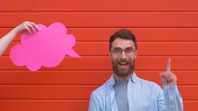 Удивленный молодой человек держит пузырь речи, смотрит камеру и усмехается, на красной предпосылке сток-видео