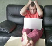 Удивленный молодой человек сидя на софе с ноутбуком в его живущей комнате стоковое фото rf