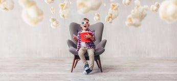 Удивленный ребенк с попкорном в стеклах 3d стоковые изображения