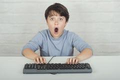 Удивленный ребенок с клавиатурой стоковые изображения