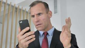 Удивленный средний достигший возраста бизнесмен сотрясенный результатом на смартфоне, интересуя