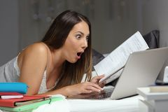 Удивленный студент находя онлайн предложение в ночи стоковое фото