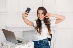 Удивленный фрилансер девушки с компьтер-книжкой и телефоном в ее руке делает selfie Молодая женщина с белой футболкой и джинсами Стоковая Фотография