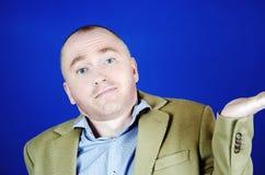 Удивленный человек в пальто сливк бросает вверх его руки к сторонам на голубой предпосылке Пустое место для вашей рекламы стоковые фотографии rf