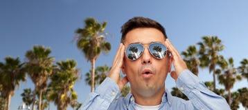 Удивленный человек в солнечных очках над пальмами стоковая фотография