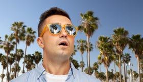Удивленный человек в солнечных очках над пальмами стоковые изображения rf
