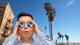 Удивленный человек в солнечных очках над пляжем Венеции стоковое изображение rf