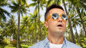 Удивленный человек в солнечных очках над тропическим пляжем стоковая фотография rf