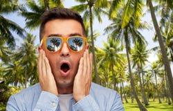 Удивленный человек в солнечных очках над тропическим пляжем стоковые фотографии rf