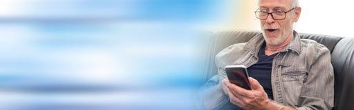 Удивленный человек смотря его телефон mobil, световой эффект Стоковое Фото