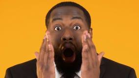 Удивленный чернокожий человек в костюме делая вау жест, возбуждая новости коммерческого рынка акции видеоматериалы