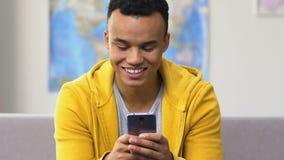 Удивленный черный смартфон просматривать старшеклассника, современные датируя социальные приложения сток-видео