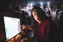 Удивленный gamer, сидя на столе около компьютера, показывает палец на экране и взгляды на камере стоковые изображения rf