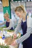 Удите продавцев tidying вверх по счетчику в магазине рыб стоковая фотография