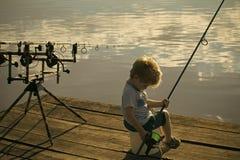 Удить, двигая под углом Милая рыбная ловля мальчика на реке Стоковая Фотография RF