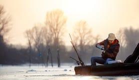 Удить на человеке льда старшем сидя на замороженном чае озера и питья стоковое изображение rf