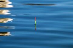 удить поплавок золотистая поверхностная вода пульсаций Отражение Стоковые Изображения RF