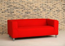 Удобная красная софа около стены Стоковое Изображение