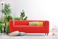 Удобная красная софа с подушками Стоковые Изображения