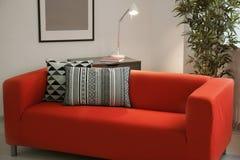 Удобная красная софа с подушками Стоковая Фотография