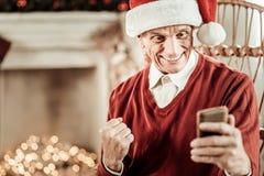 Удовлетворенное удивленное ликование человека и удержание его мобильного телефона стоковое фото