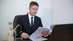 Удовлетворенные печатные документы чтения юриста на его таблице работы акции видеоматериалы