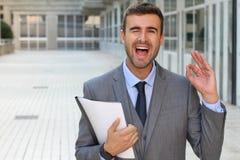 Удовлетворенный бизнесмен давая положительный wink стоковые фото