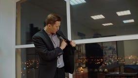 Удовлетворенный бизнесмен кладя стог денег во внутренний карман куртки в офисе видеоматериал