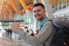 Удовлетворенный давать путешественника большие пальцы руки вверх от авиапорта стоковое фото rf