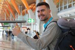 Удовлетворенный давать путешественника большие пальцы руки вверх от авиапорта стоковые изображения