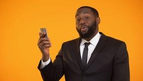 Удовлетворенный с большими пальцами руки-вверх мобильного представления применения черными мужскими показывая видеоматериал