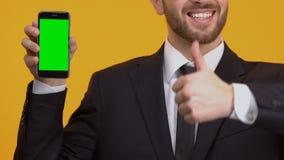 Удовлетворенный с человеком нового применения показывая большие пальцы руки-вверх, зеленый смартфон экрана сток-видео