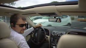 Удовлетворенный человек в купленном костюме новым автомобилем и большими пальцами руки показывать вверх показывать, испытывает пр видеоматериал