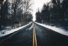 Уединённая дорога идя в расстояние во время зимы Стоковые Фотографии RF