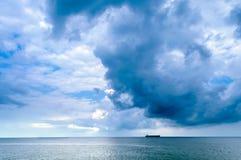 Уединённый корабль в море при темные облака маяча сверх Стоковая Фотография RF