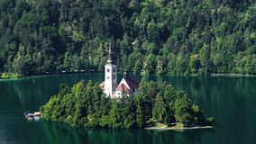 Уединённый остров при церковь окруженная озером кровоточил и Альпы, духовность стоковое фото rf