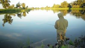 Уединённый рыболов бросает рыболовную удочку Он один с природой сток-видео