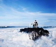 Уединённый бизнесмен работая на удаленном утесе стоковое изображение rf