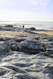 Уединённый человек идя на скалистый пляж Стоковое фото RF