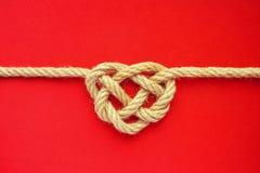 Узел веревочки формы сердца на красной предпосылке Узел celtic веревочки джута Стоковые Изображения