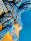 Узел сделанный голубой переплетенной веревочки в песчинках, весьма конца вверх стоковое изображение
