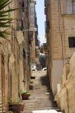 Узкая идя улица в старом городке Валлетты, Мальты. стоковые изображения