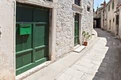 Узкая улица в старом среднеземноморском городке с зелеными дверями на белизне, облицовывает построенный фасад Стоковое Изображение