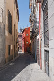 Узкая улица с красным зданием в Мадриде, Испании Стоковая Фотография RF