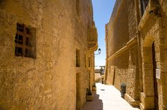 Узкие каменные улицы с желтыми зданиями в старом средневековом замке башни Cittadella, также известном как цитадель, Castello в стоковая фотография rf