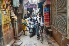 Узкие улицы Священного города Варанаси с велосипедистами и проезжий- стоковое изображение rf