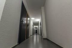 Узкий белый коридор с много дверей в жилом доме Стоковое Фото