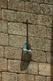 Узкий разрез в перекрестной форме и сточная канава на каменной стене стоковое фото rf